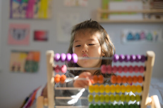 Little kid doing math (abacus)
