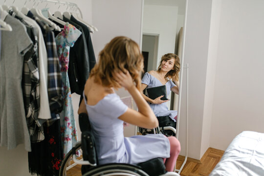Young woman in a wheelchair choosing clothes from a clothes rack in her bedroom