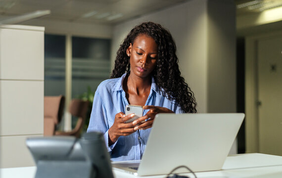 Serious black woman taking notes in smartphone during work in office