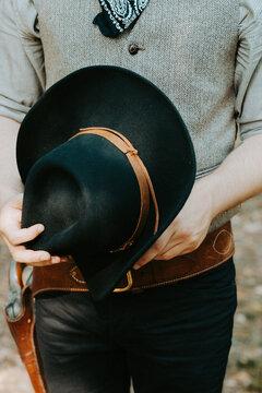 close up of a man holding a black cowboy hat