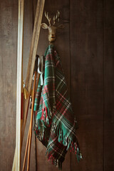 Old skis and poles against wall with green plaid blanket