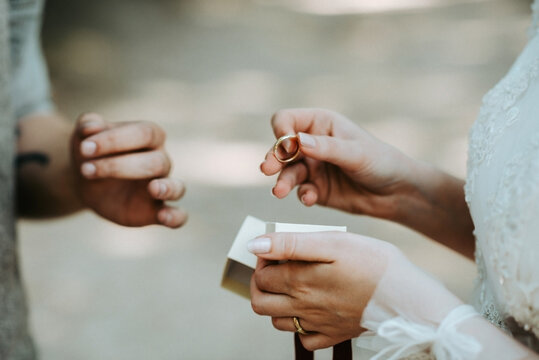 Bride holding a golden wedding ring on the wedding ceremony