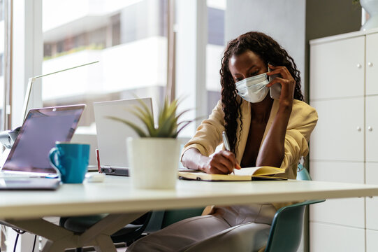 Busy black woman in mask working in office