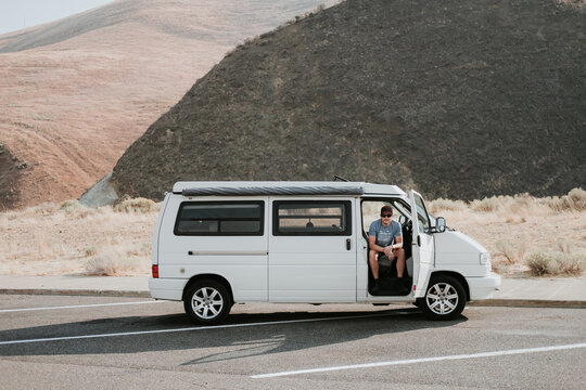 Man sits in white van in a parking lot in the desert.