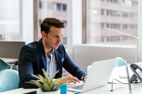 Focused businessman working on laptop in office