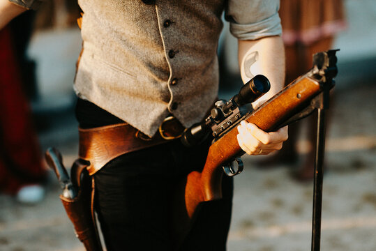 close up of a cowboy holding a big gun in his hands and loading it