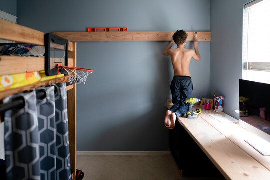 Boy nails board to bedroom wall