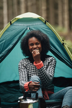 Laughing woman eating a snack while camping