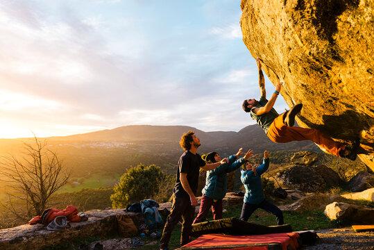 Man climbing granite boulder rock near friends