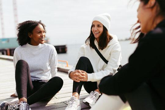 Women talking on a dock after a run