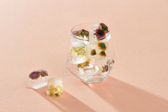 Ice cubes with flowers and glass bowl on color background