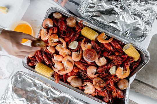 A hand reaching for Crawfish / Crayfish and boiled shrimp and corn