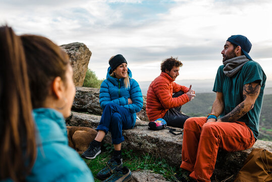 Group of cheerful friends resting on rocky mountain