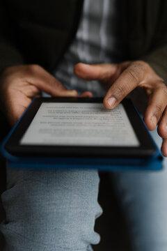 Black hands Holding an E-Book Tablet