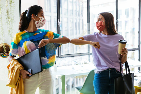 Young multiethnic women in masks bumping elbows in workspace during coronavirus pandemic