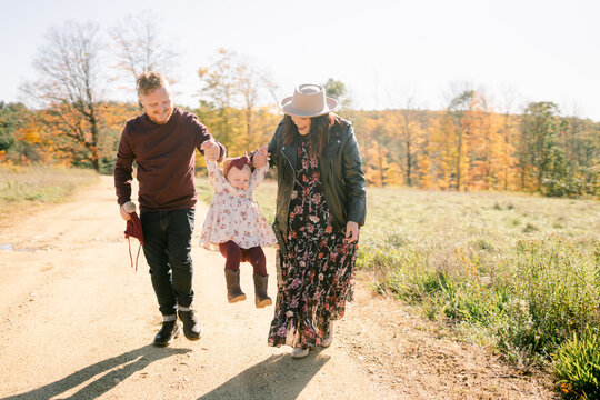 happy toddler walking between her mom and dad