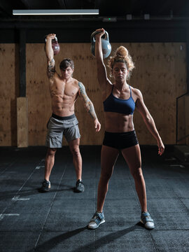 Young man and woman weightlifting in a gym