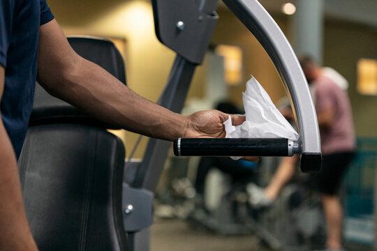 Gym: Man Wipes Down Equipment Handle