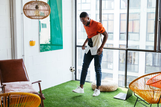 African American employee playing with ball in workspace