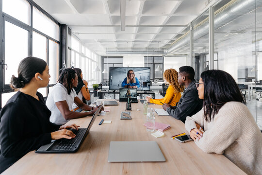 Group of multiracial businesspeople sitting around table having a remote video conference in modern workplace