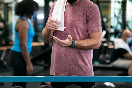 Gym: Man Uses Hand Sanitizer While Working Out
