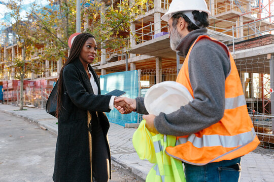 Woman engineer shaking hand with construction foreman of building in development