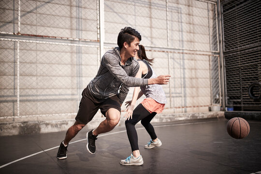 young asian man and woman playing basketball for fun