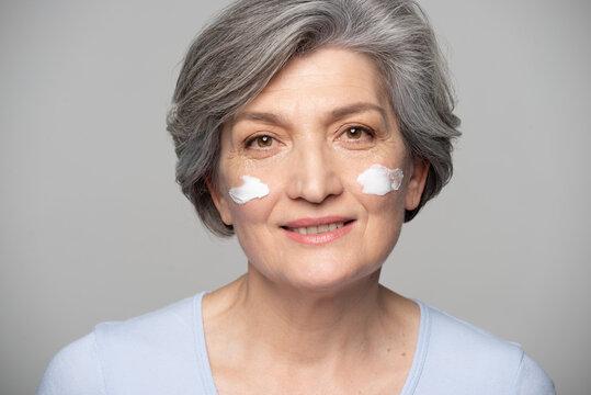 Mature Woman Applying Facial Cream