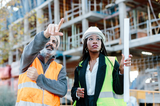 Construction worker talking with woman engineer in front of a construction area