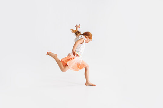 Young girl running through a white background.