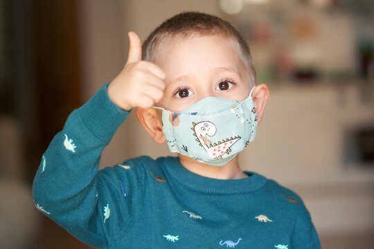 Positive kid in mask showing thumb up