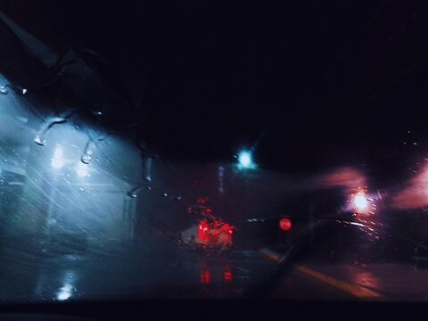 street scene shot in the rain at night through the windshield featuring a car with their break lights on.