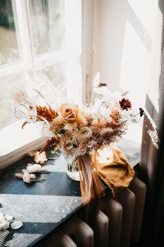 wedding bouquet with orange tones on a window sill
