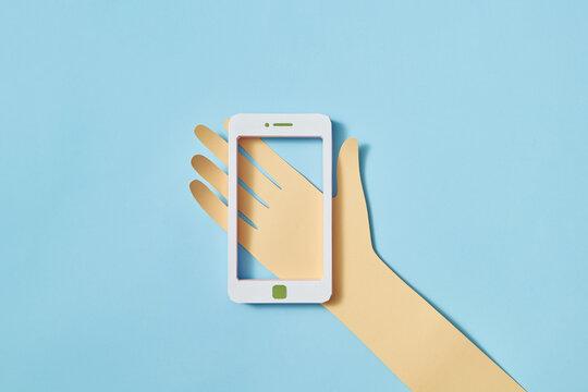 Papercraft hand holds handmade smartphone frame.