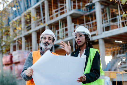 Woman engineer giving instructions to construction worker based on blueprints.
