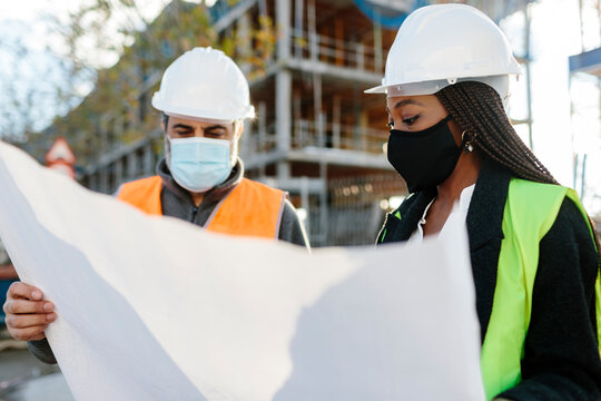 Woman engineer supervising construction of building with construction worker.