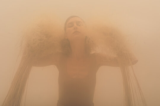 Woman with dry plants in fog