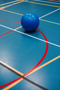 Flooring of a sports hall with different kind of lines and blue yoga ball