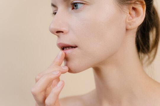 Charming woman applying lip balm in studio