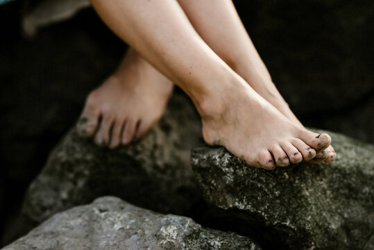 Barefoot with sand on their toes