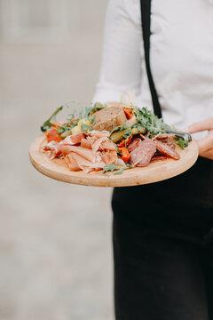 Waiter serving tapas on a wooden server