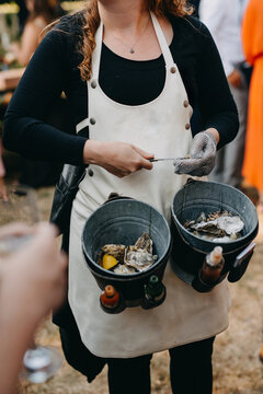 Waiter with oysters outdoors on a gathering
