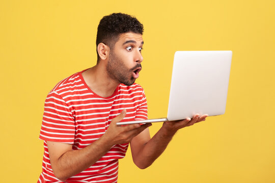 Profile portrait shocked surprised man with beard in striped t-shirt holding laptop and looking at display with big astonished eyes. Indoor studio shot isolated on yellow background