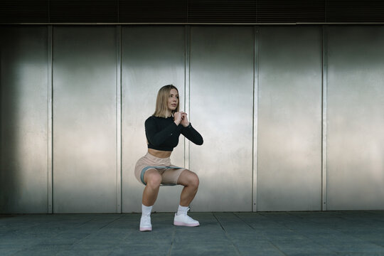Woman doing a squat with resistance bands