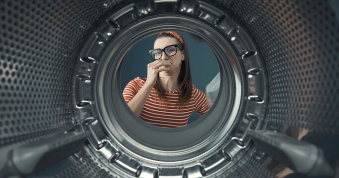 Woman looking into her smelly washing machine