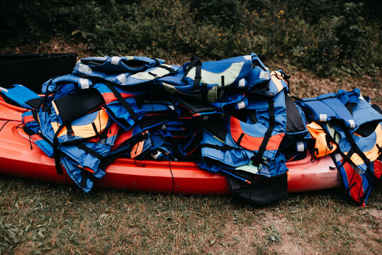 Red canoe with a bunch of life jackets stacked on top