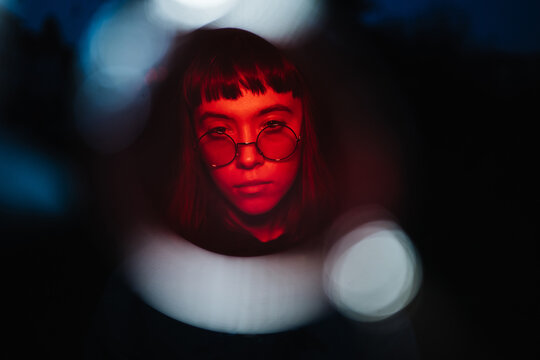 Young woman wearing sunglasses in red light