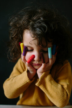 Portrait of sweet kid resting her head on her hands over dark background with marker caps on her fingers