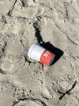 FRESNO, UNITED STATES - Feb 28, 2021: A red and white empty cup on the sand as trash (space for text)