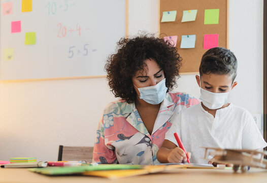 Teacher woman with child wearing face protective mask in preschool classroom during corona virus pandemic - Healthcare and education concept